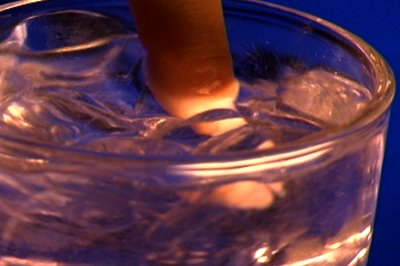 stock-footage-finger-stirring-a-glass-of-water-with-ice-cubes